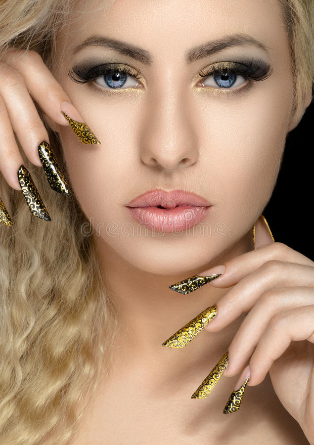 Capelli e tema di trucco: bella ragazza con la bella unghia dorata nello studio fotografie stock libere da diritti
