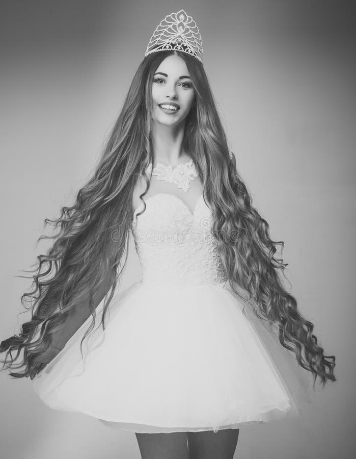Capelli eleganti La ragazza ha il trucco alla moda e capelli sani su fondo grigio immagini stock libere da diritti