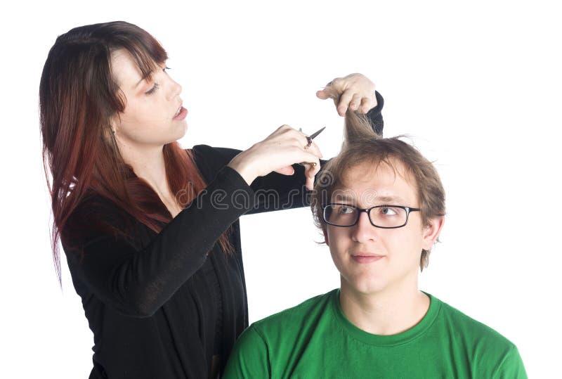 Capelli femminili di taglio del parrucchiere di un cliente maschio immagine stock