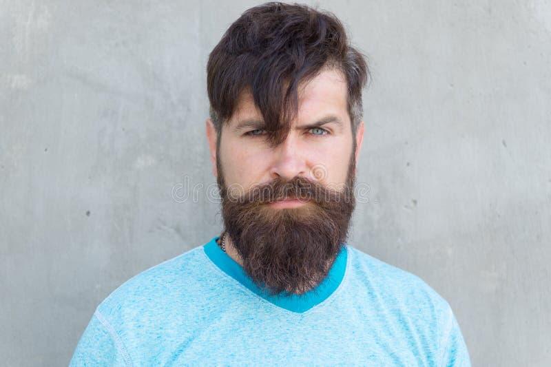 Capelli lunghi Colpi tagliati Pantaloni a vita bassa freschi con taglio di capelli di bisogno della barba Salone del barbiere e c fotografia stock