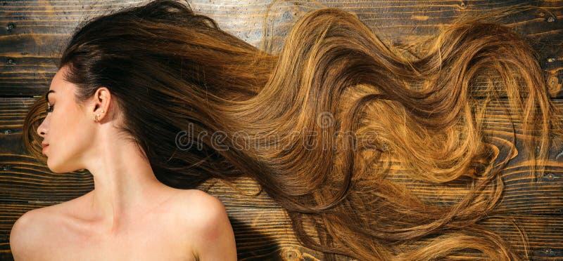 Capelli molto lunghi su fondo di legno Bello modello con l'acconciatura riccia Concetto del salone di capelli Cura e prodotti per fotografia stock