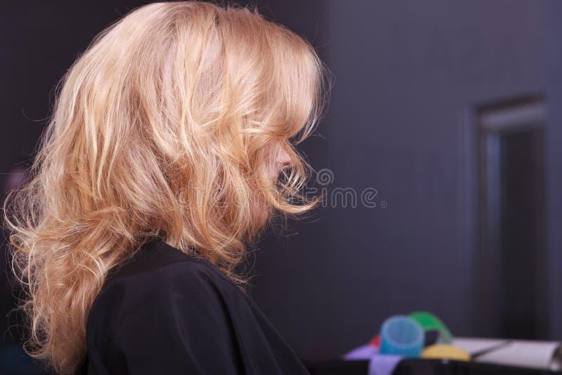 Capelli ondulati biondi femminili. Indietro della testa della donna. Parrucchiere. Salone di bellezza. fotografie stock