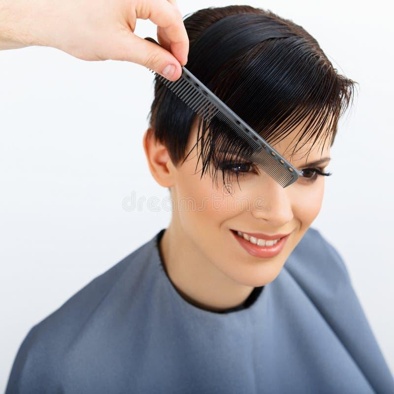 Capelli. Parrucchiere che fa acconciatura. Bellezza Woman di modello. Taglio di capelli. immagini stock libere da diritti