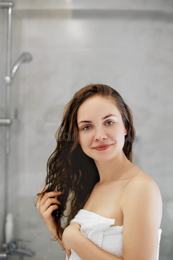 capelli Ragazza che tocca i suoi capelli ed attimo sorridente che guardano nello specchio Ritratto della giovane donna felice con fotografia stock libera da diritti
