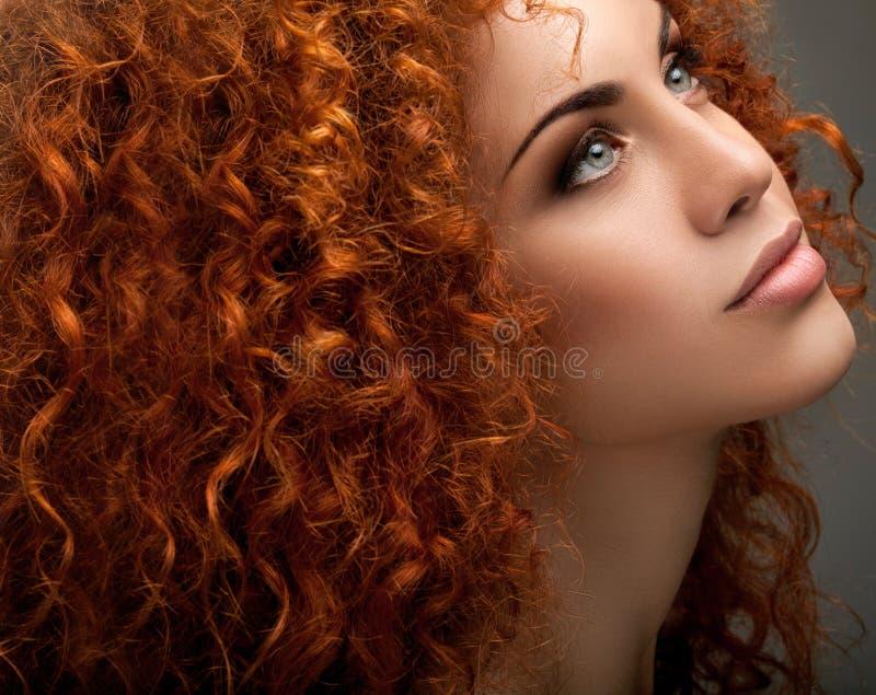 Capelli rossi. Bella donna con capelli lunghi ricci. immagine stock