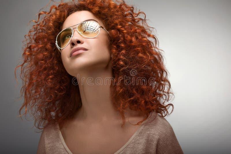 Capelli rossi. Bella donna con capelli lunghi ricci e Sunglases fotografia stock libera da diritti