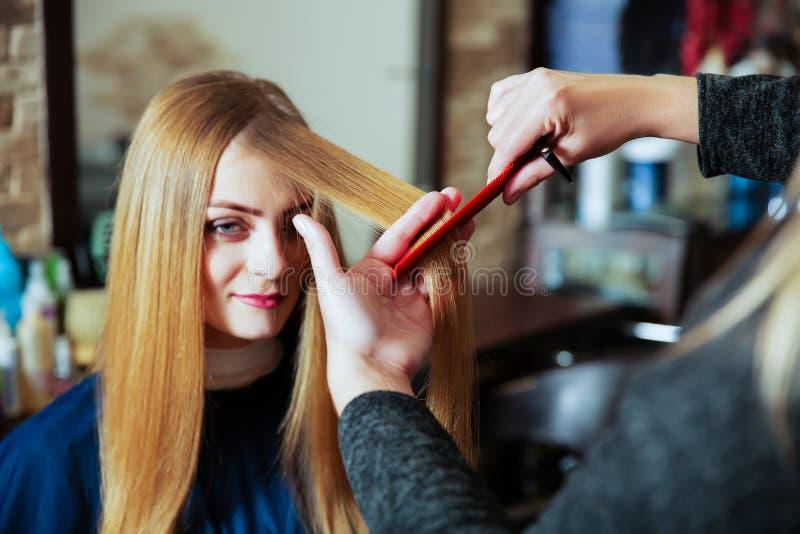 Capelli svegli del parrucchiere alla giovane donna fotografia stock libera da diritti