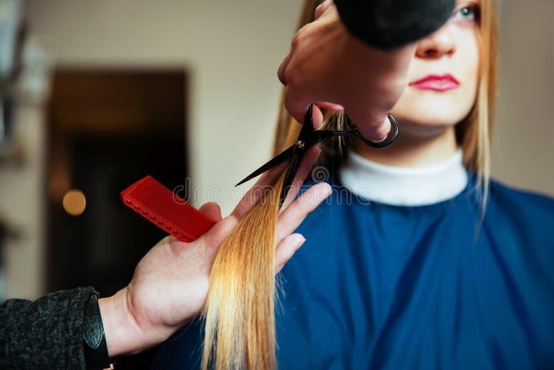 Capelli svegli del parrucchiere alla giovane donna fotografia stock
