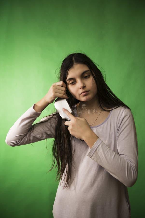 Capelli teenager del pettine della ragazza immagine stock libera da diritti