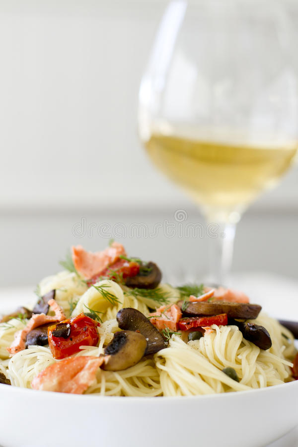 Capellini Pasta with Salmon and Vegetables. Salmon pasta with tomatoes, capers, and mushrooms stock photo