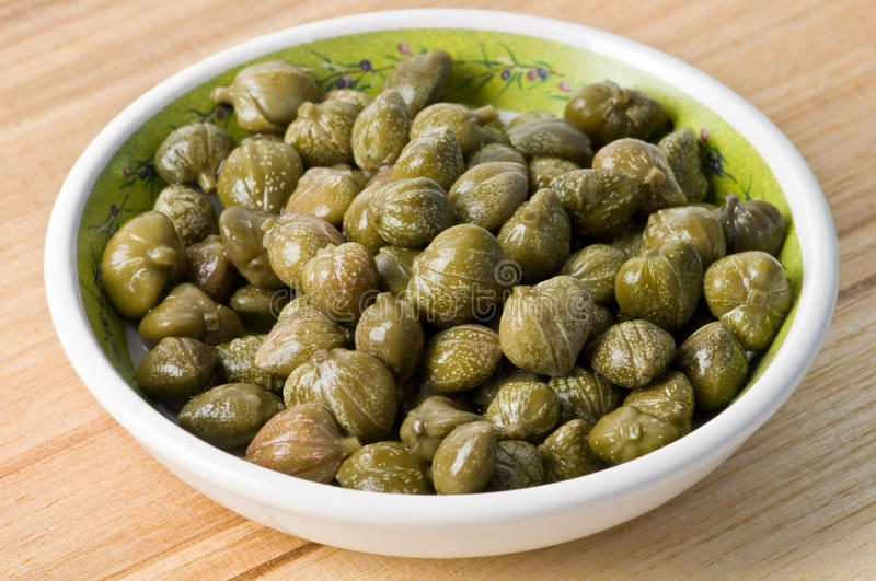Capers. In plate on wood table stock photography