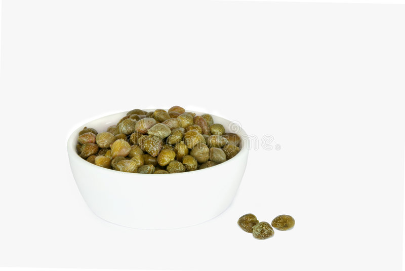 Capers. In a china bowl with three loose , over white background royalty free stock photography