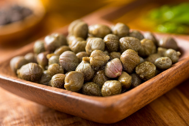 Capers. Pickled capers in a wooden serving bowl with basil and black peppercorns royalty free stock image