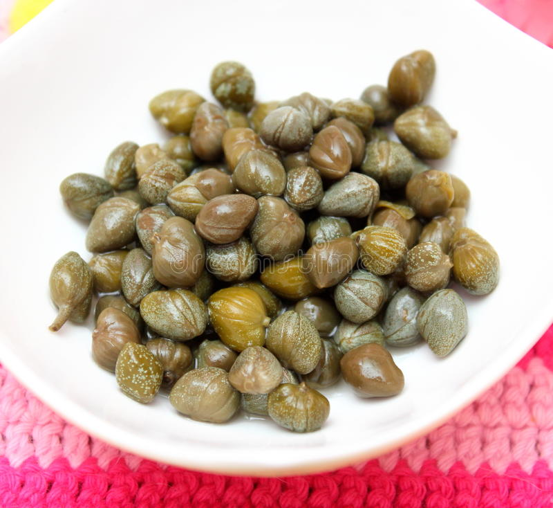 Capers. Some green capers in a bowl royalty free stock image