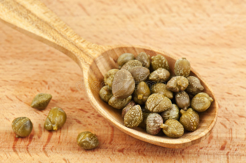 Capers in wooden spoon. Delicious capers in wooden spoon stock image