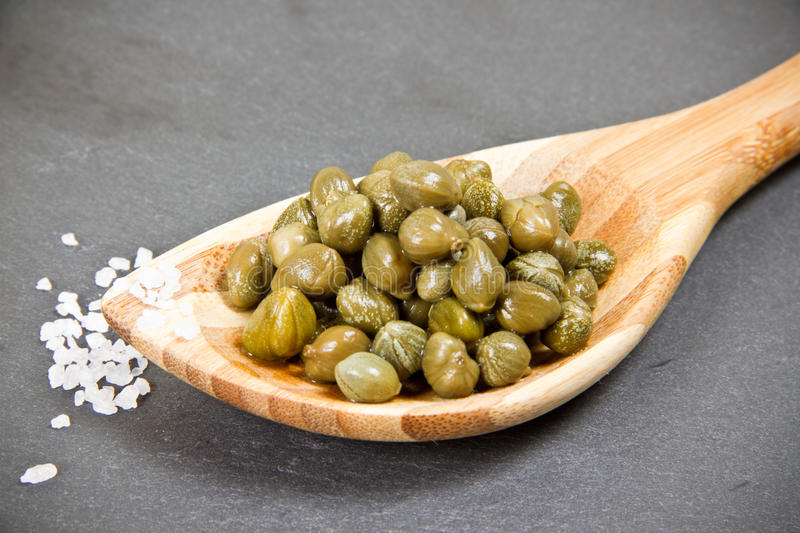 Capers. On wooden spoon with seasalt royalty free stock photos
