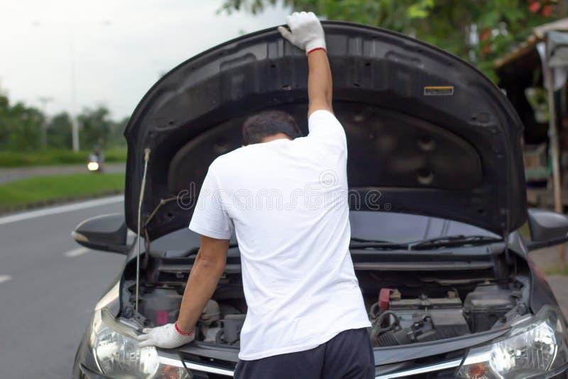 Capilla abierta del coche de los guantes del mecánico que lleva que comprueba el wh del aceite de motor de coche imagen de archivo libre de regalías