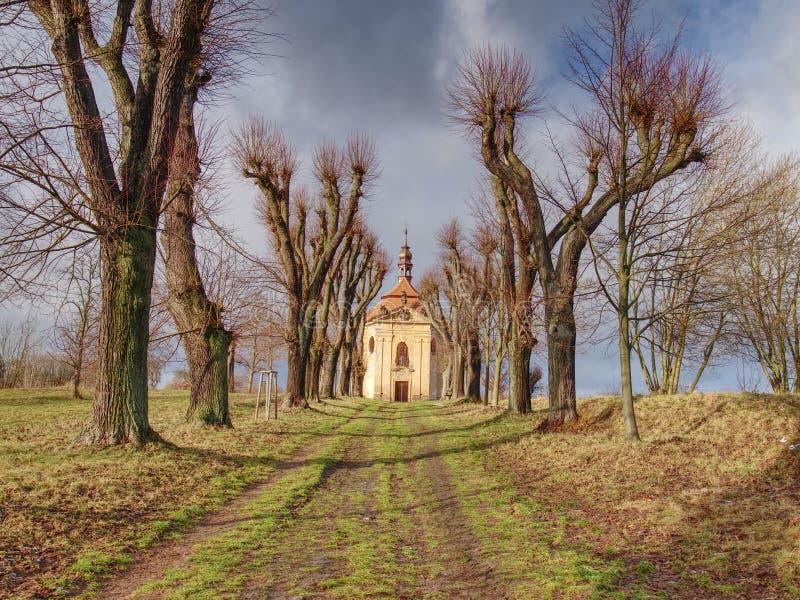 Capilla con los árboles del otoño en el extremo del camino del callejón imágenes de archivo libres de regalías