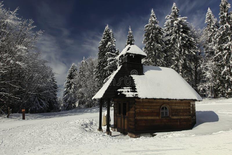 Capilla de madera cerca de un bosque nevoso imagen de archivo