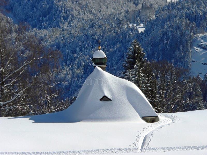 Capilla sitiada por la nieve en las montañas austríacas imagenes de archivo