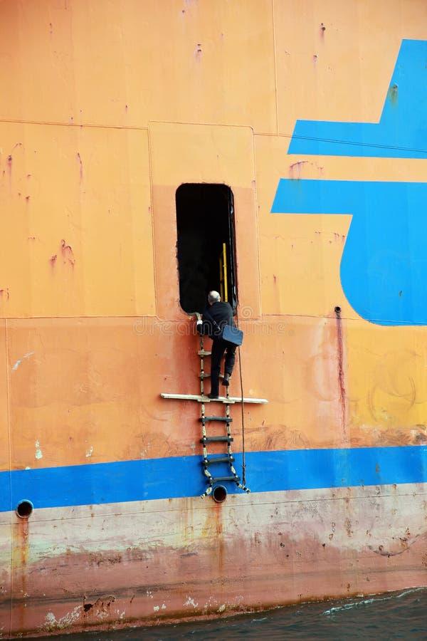 Capitán de la guía del mar que viene en la nave industrial imagen de archivo