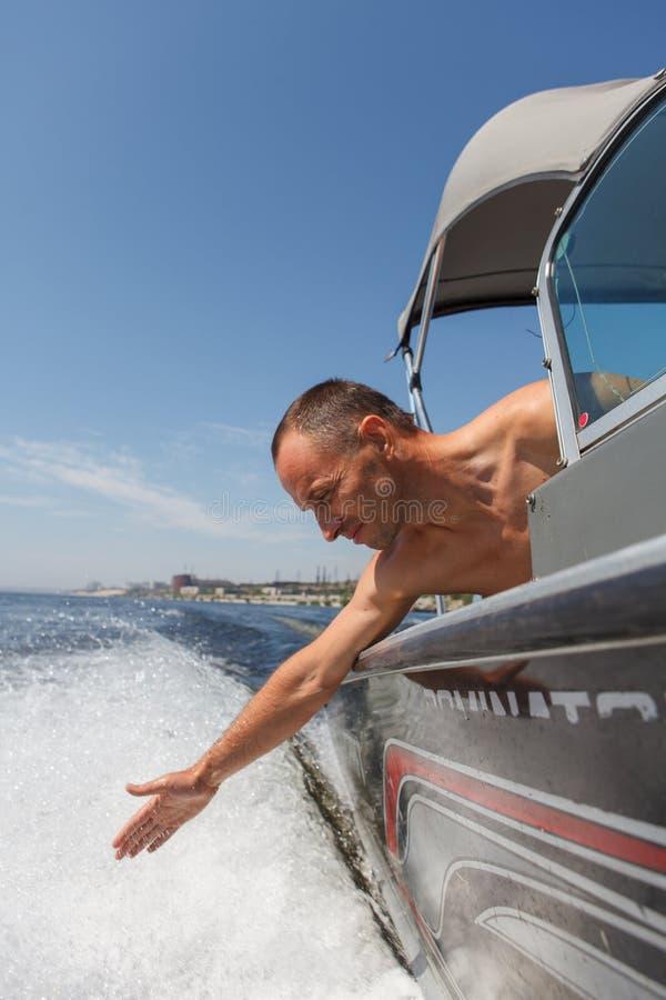 Capitán que conduce un barco en un río imagen de archivo