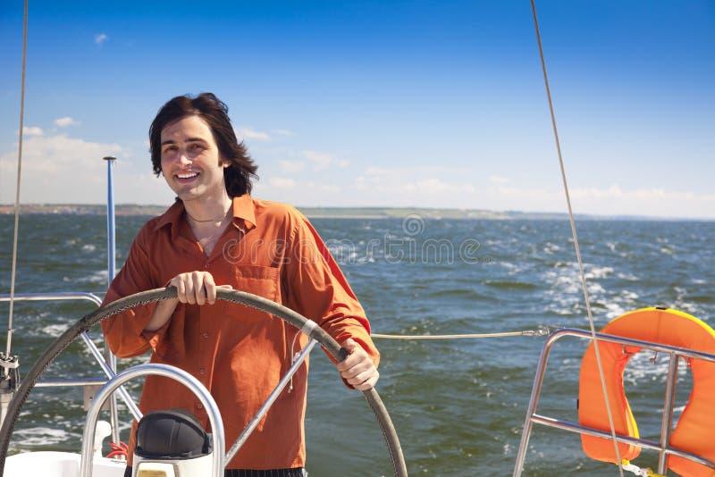 Capitão dos jovens que conduz o sailboat imagem de stock