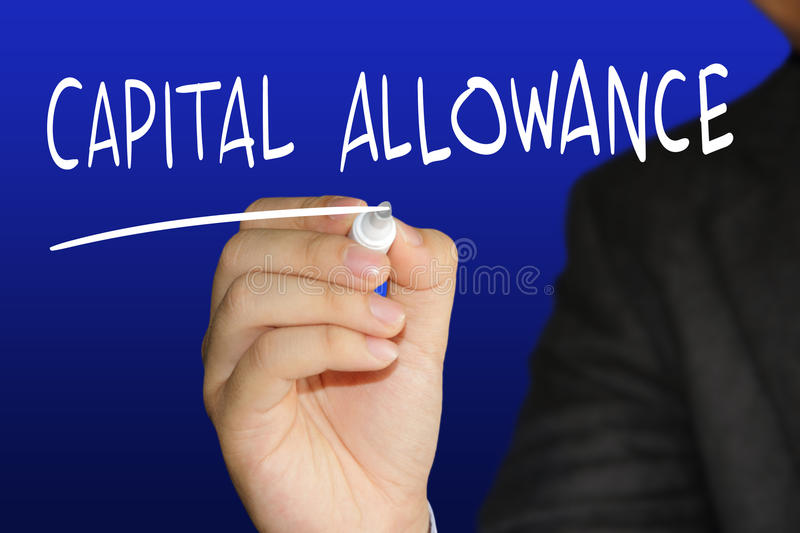 Capital Allowance. Business concept image of a businessman holding marker and write Capital Allowance over blue background royalty free stock photography
