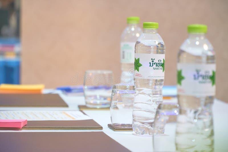 Capital de Vientiane, Laos - 5 de abril de 2019: As garrafas de água na tabela com vidros e notas de papel coloridas na sala de  imagem de stock royalty free