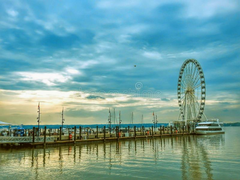 Capital Ferris Wheel At The National Harbor In Maryland. Amusement, pier, potomac, river, travel, destination, waterfront, boat, dock, seascape, usa, sunset stock photography