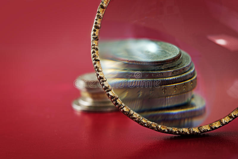 Capital increase, magnifying glass in front of a small coin stack, symbol for accurate check at financial investment, red stock image
