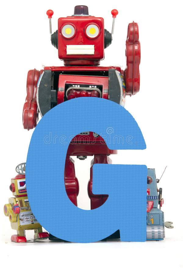 Big let G held by vintage robot toys. Capital letter blue G held by vintage robot toys royalty free stock photo