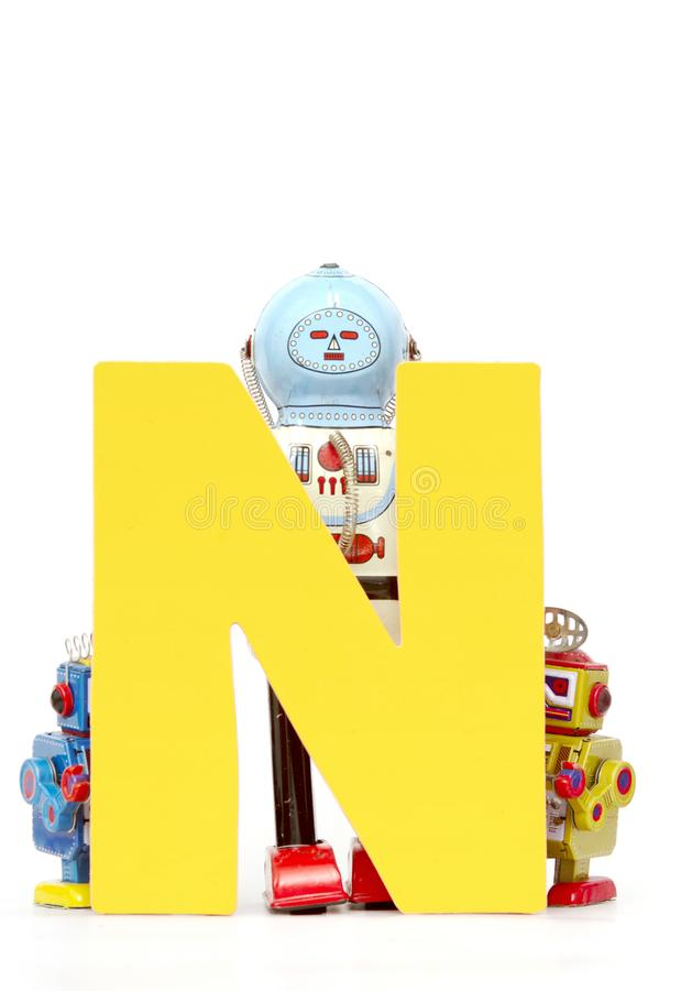 Big letter yellow N held by vintage robot toys. Capital letter yellow N held by vintage robot toys on white stock image