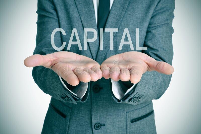Capital nas mãos de um homem de negócios foto de stock royalty free