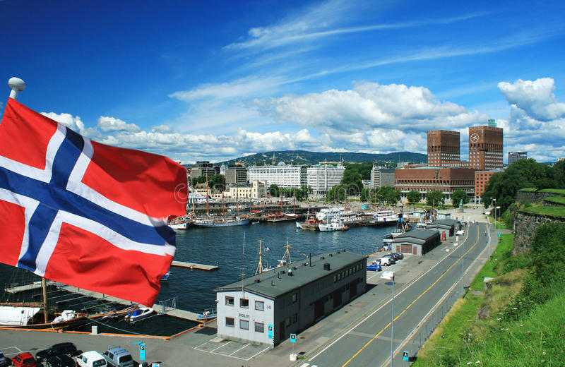 Capital of Norway - Oslo with flag. Flag of Norway with capital city - Oslo in background during sunny day stock image