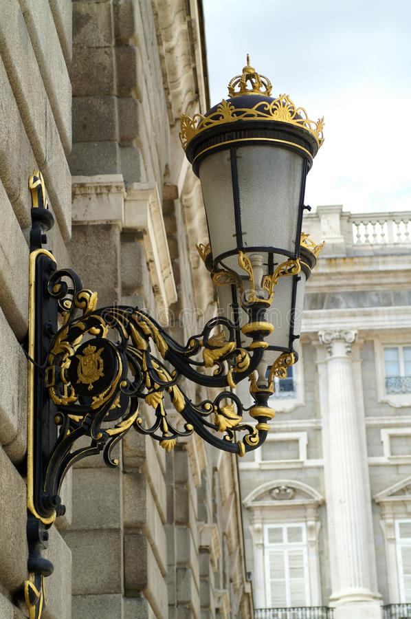 Street lamp on the wall of the royal palace in Madrid royalty free stock images
