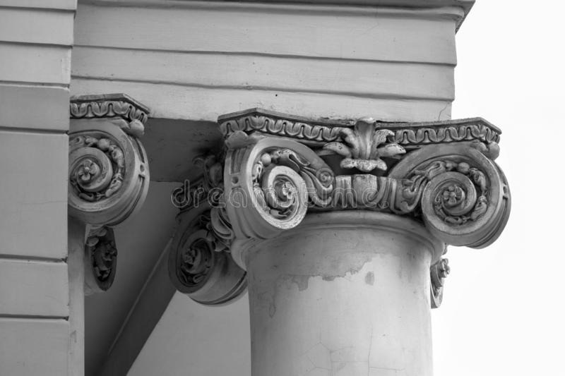 Capital - the upper part of the column close-up. Neoclassical style building element. Black and white photo royalty free stock photo