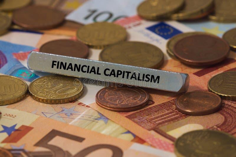 capitalismo financeiro - a palavra foi imprimida em uma barra de metal a barra de metal foi colocada em diversas cédulas imagens de stock