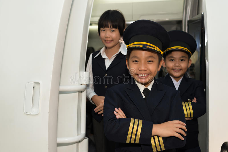 Capitan and cabin crew. Portrait of little smiling capitan with cabin crew in the airplane royalty free stock photography
