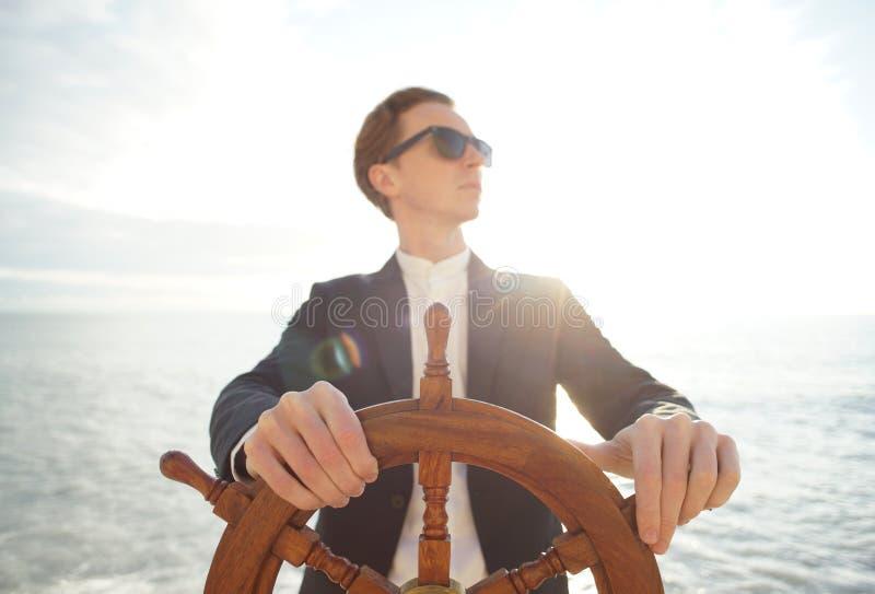 capitano Mani sul timone della nave fotografie stock