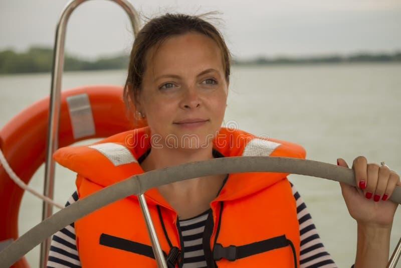 Capitano sveglio della giovane donna nel giubbotto di salvataggio al timone dell'yacht immagini stock