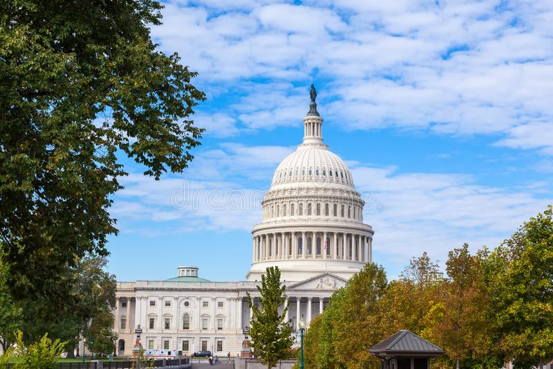 Capitol USA Building at day.Yellow-green trees in autumn. White feather clouds and blue. Sky. United States Congress. Washington DC, USA stock images