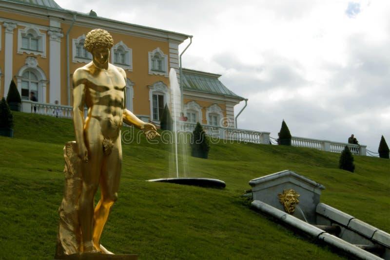 Capitoline Antinous被镀金的雕象反对象草的倾斜与喷泉和大Peterhof宫殿的在圣彼德堡,俄罗斯 图库摄影