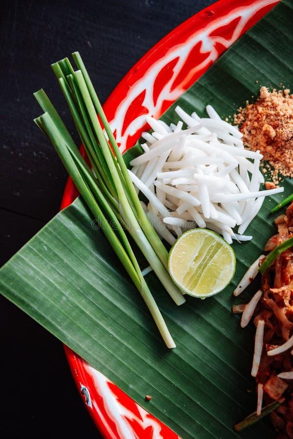 Capitonnez la garniture thaïlandaise comprenant la chaux, oignons blancs, pousses de haricot poudre écrasée d'arachide et de pime photos libres de droits