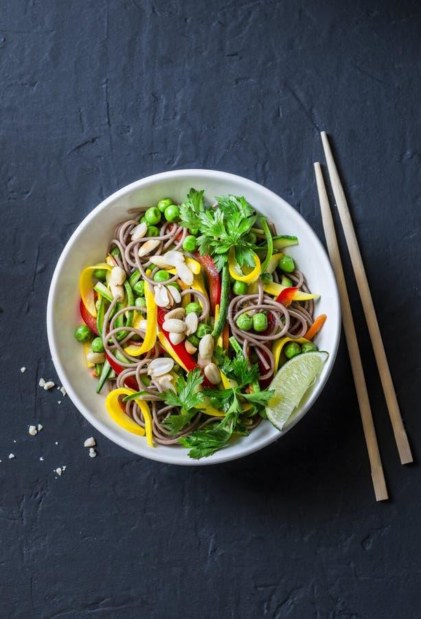 Capitonnez les nouilles thaïlandaises de soba de légumes sur le fond foncé, vue supérieure Nourriture végétarienne saine images libres de droits