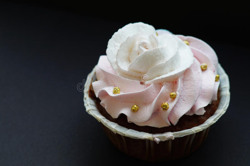 Capkake with a rose from a white and pink cream with gold beads. stock images
