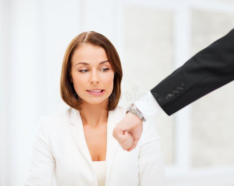 Capo che mostra tempo alla donna di affari sollecitata fotografia stock libera da diritti