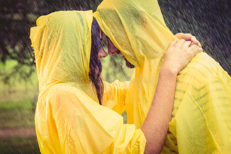Capo d'uso di protezione delle coppie sveglie ed abbracciare sotto la pioggia immagini stock libere da diritti