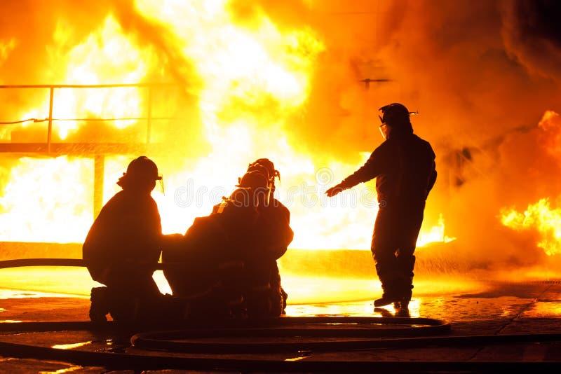 Capo dei vigili del fuoco che dà istruzioni ai pompieri durante l'esercizio antincendio fotografie stock libere da diritti