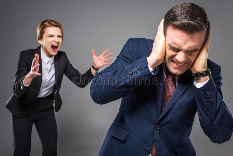 capo femminile aggressivo che urla all'uomo d'affari spaventato, immagini stock